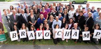 Groupe de gens posant avec des affiches sur lesquelles on peut lire « Bravo CHAMP ».