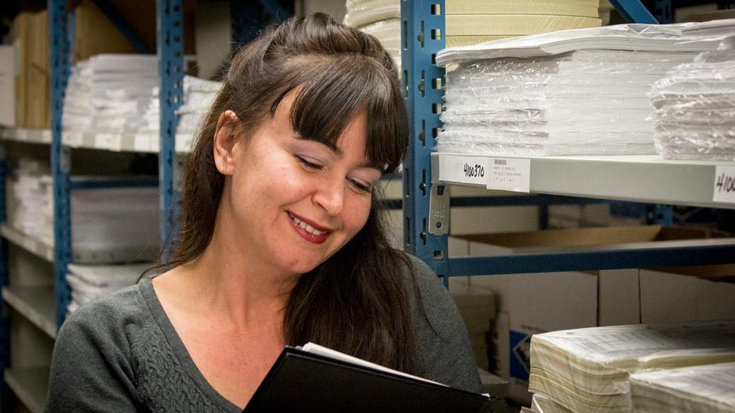 Femme appuyée contre une étagère remplie de formulaires