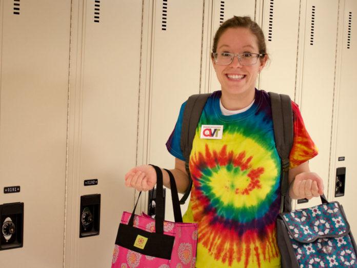 Jeune femme au chandail coloré tenant sa boîte à lunch