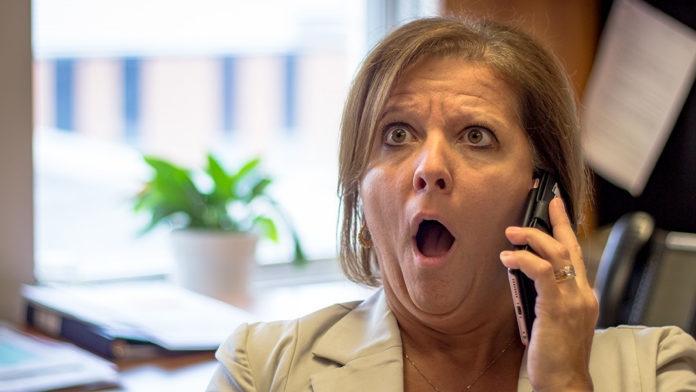 Femme surprise en parlant au téléphone.