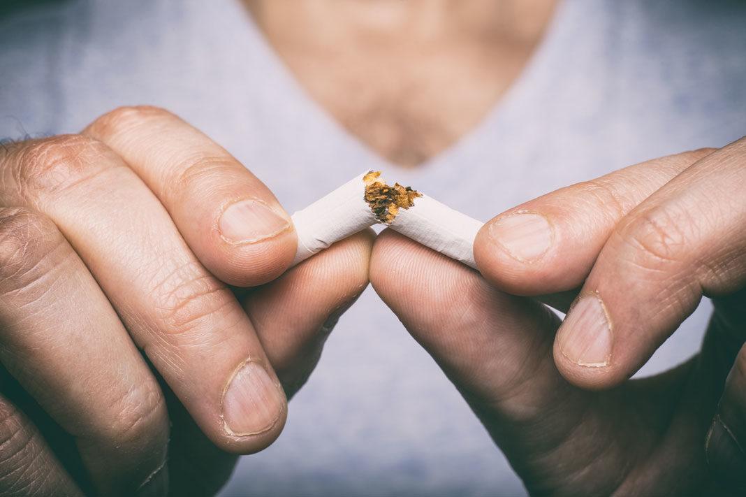Plan rapproché des doigts qui casse une cigarette en deux.