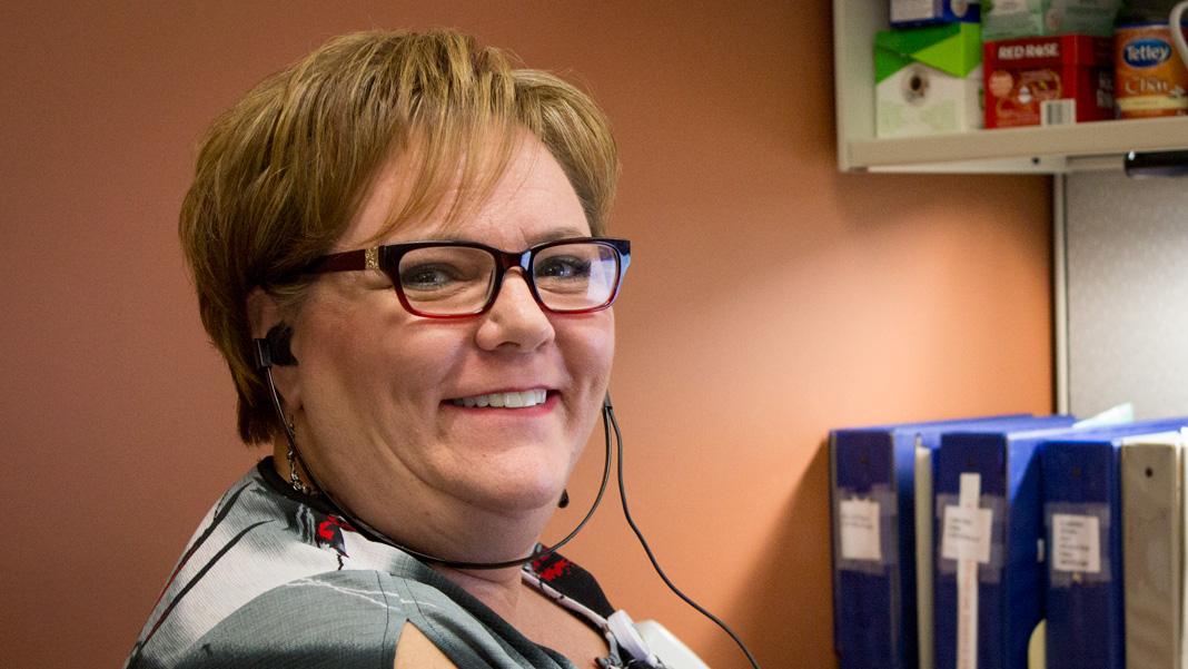 Femme assise à son poste de travail, portant des écouteurs utilisés pour la transcription médicale.