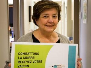 Femme tenant fièrement une affiche sur laquelle on peut lire : Combattons la grippe! Recevez votre vaccin.