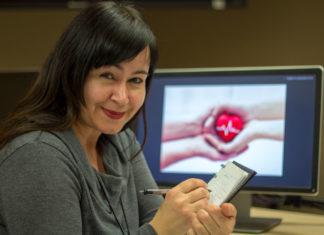 Femme en train d'écrire dans un cahier, en étant assise devant un écran d'ordinateur.
