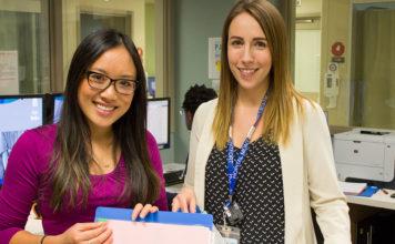 Deux pharmaciennes consultent un cartable au poste infirmier