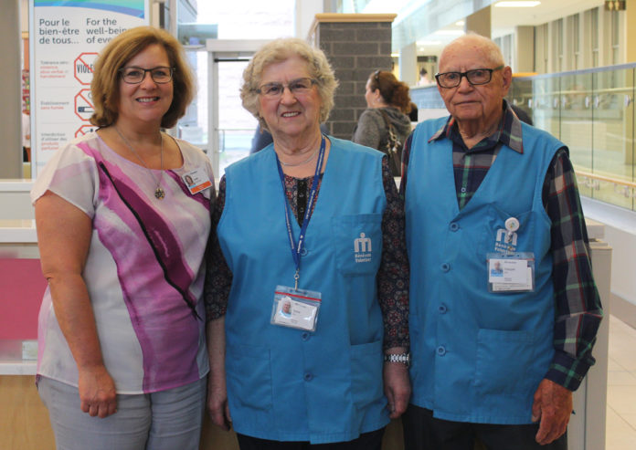 Trois adultes dans l'entrée principale de l'hôpital qui sourient