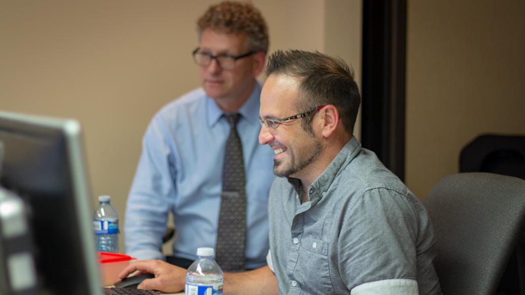 Deux hommes regardent un écran d'ordinateur
