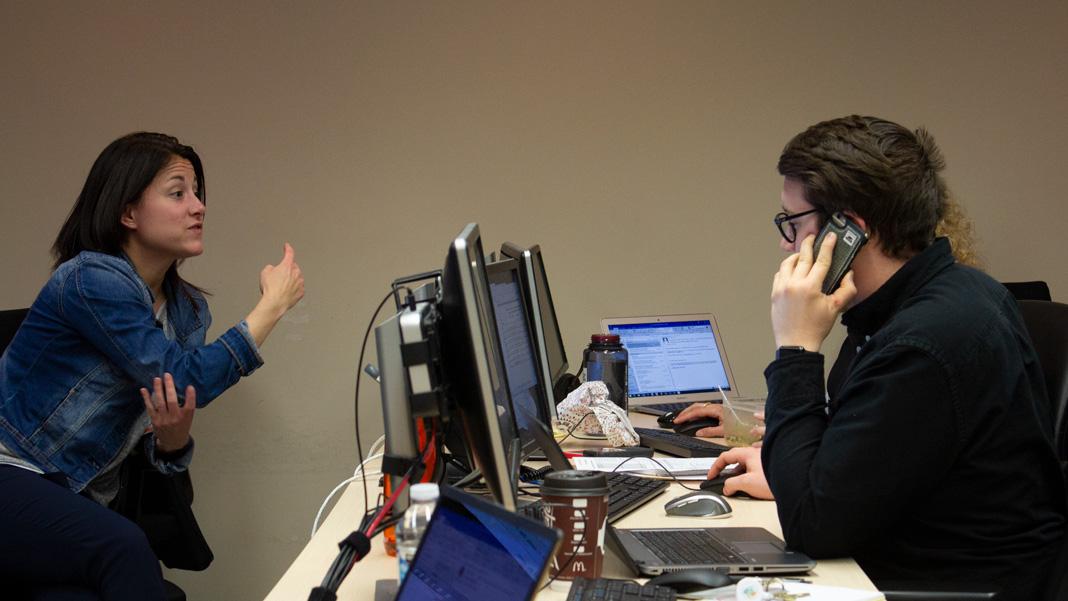 Groupe de gens à l'ordinateur discutant entre eux