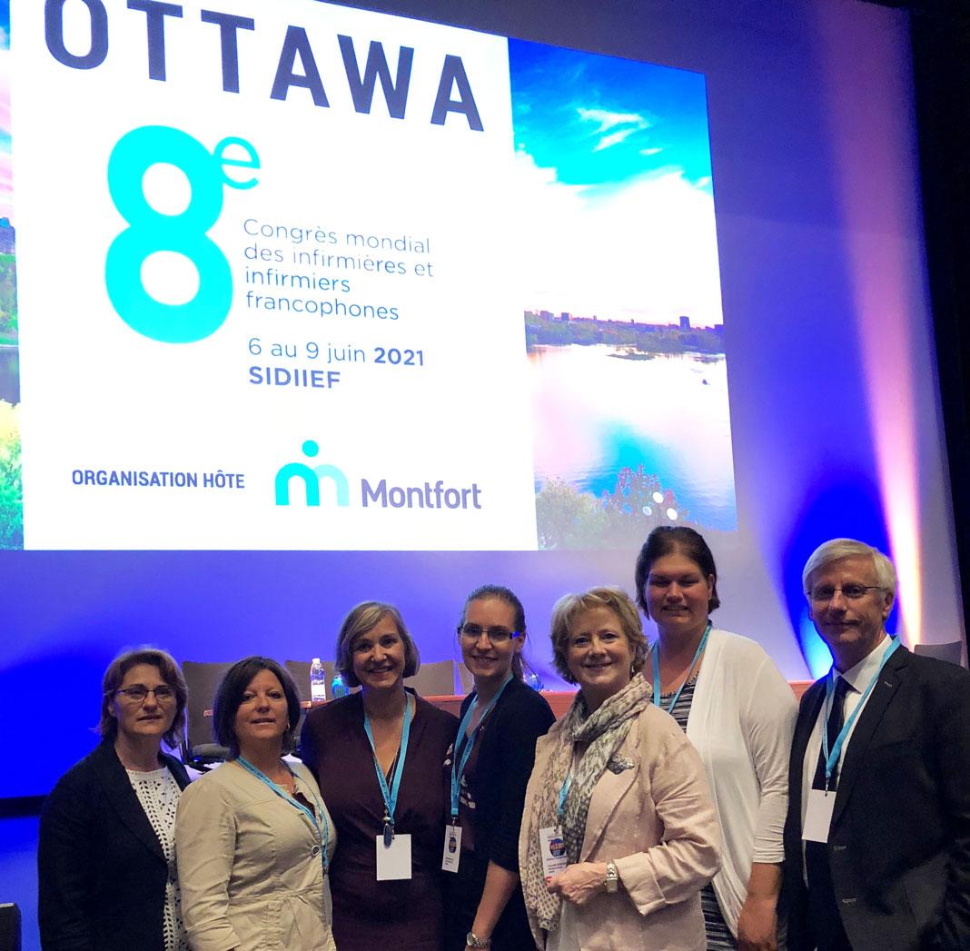 Six femmes et un homme sur un estrade à une conférence