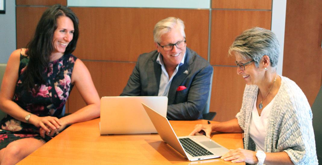 Deux femmes et un homme en rencontre à une table avec leurs ordinateurs portables
