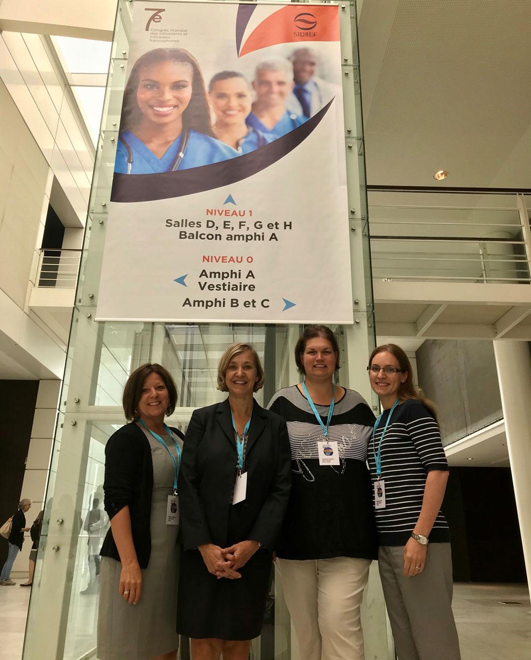4 femmes debout devant une bannière de conférence du SIDIIEF