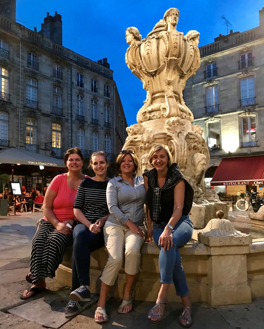 4 femmes assises sur le bord d'une fontaine