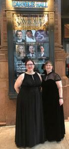 Deux femmes en robes noires devant une affiche illuminée