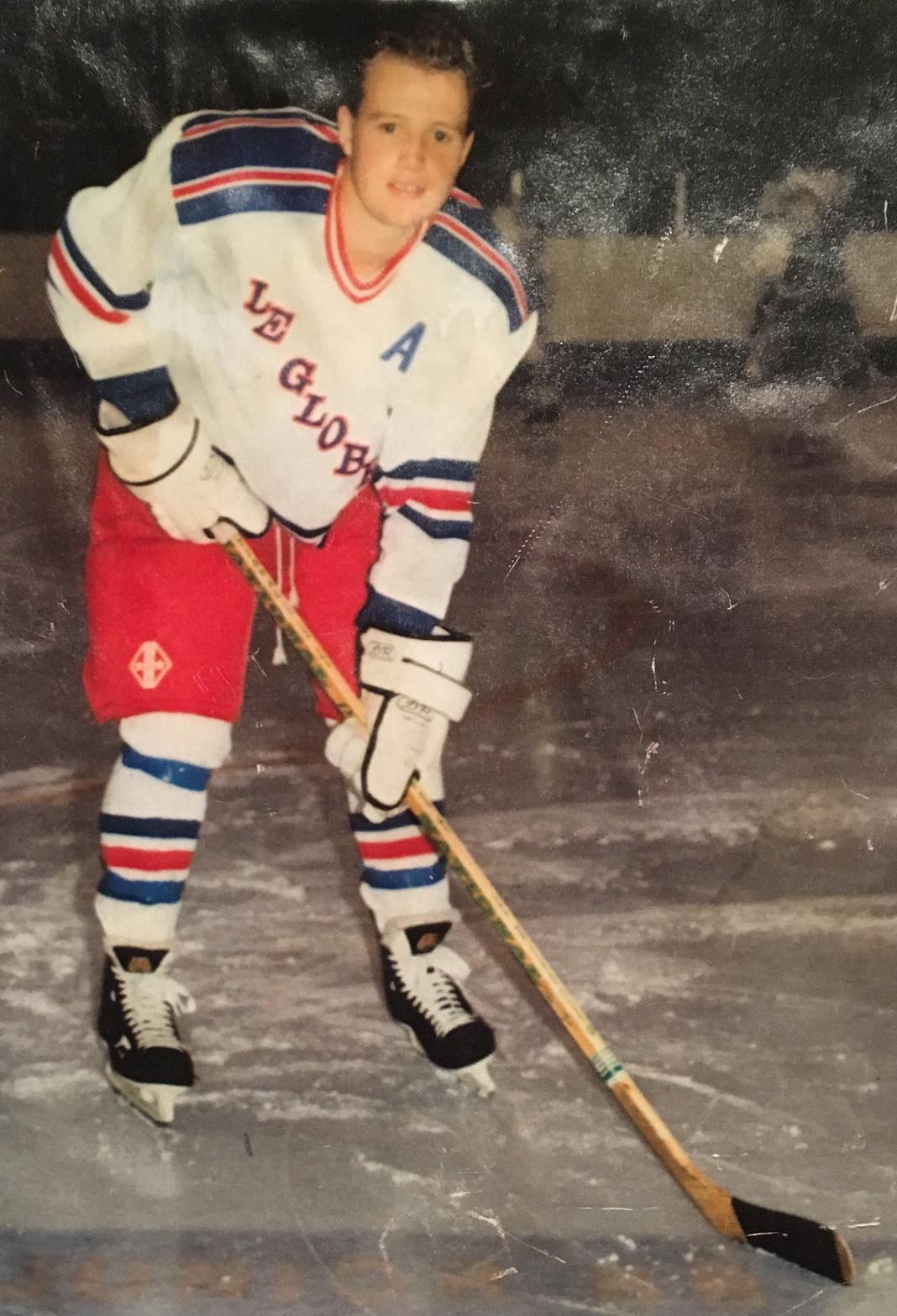 Jeune homme tenant un bâton de hockey sur une patinoire
