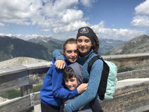 Trois enfants souriants devant des montagnes