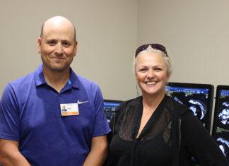 Deux professionnels devant des écrans où l'on voit des images d'examens d'imagerie médicale.