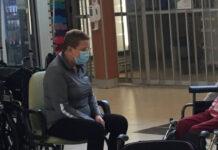 Une dame avec un masque assise sur une chaise