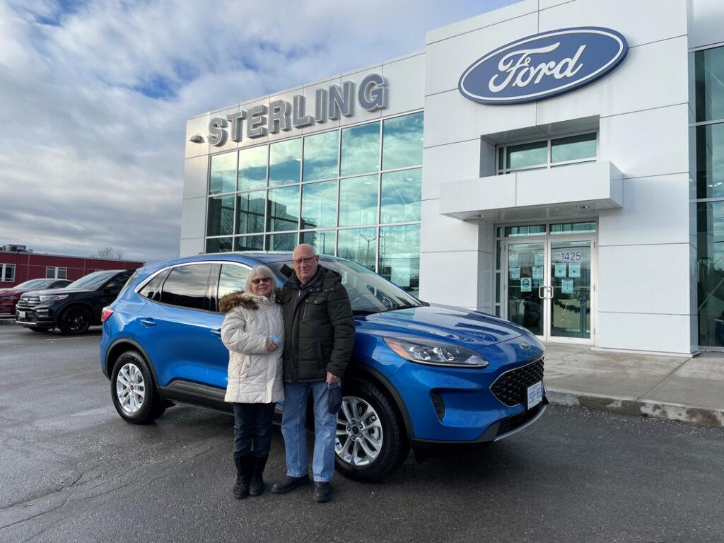 Homme et femme devant une voiture bleue chez un concessionaire