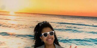 Femme noire avec lunettes de soleil devant une murale