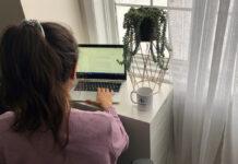 Femme qui tape à son ordinateur portable devant une fenêtre