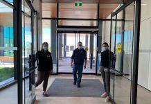 Deux femmes qui ouvrent les portes d'un édifice vitré et un homme qui entre. Tous masqués.