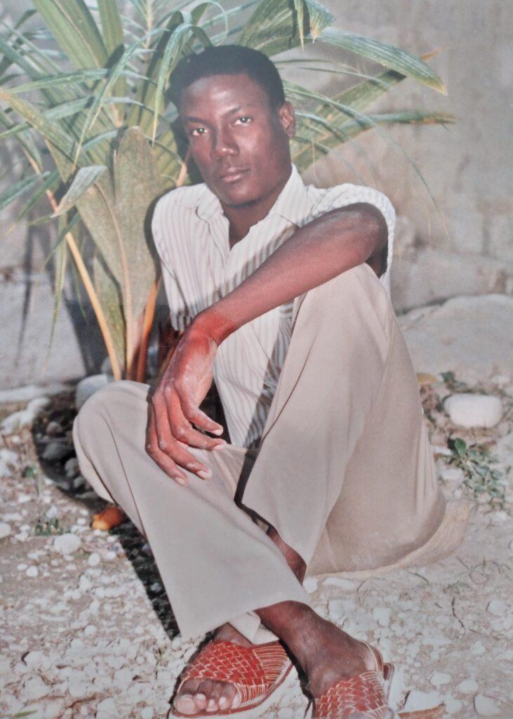 Jeune homme assis sous un palmier